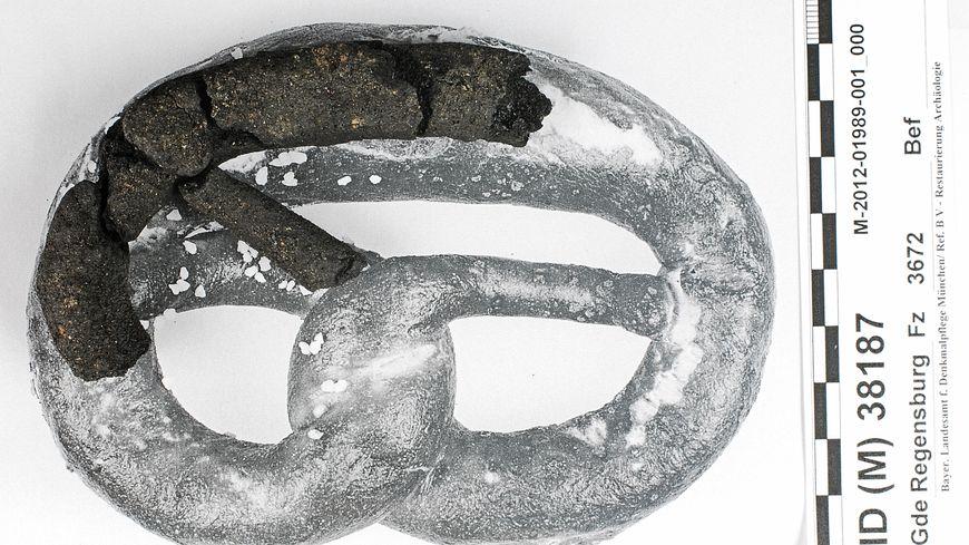 Les fragments du plus vieux bretzel du monde posés sur une photo de bretzel.