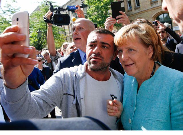 Angela Merkel pose auprès de réfugiés arrivés fraîchement en Allemagne.