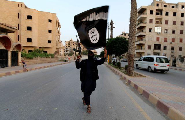 Un membre de Daech agite un drapeau à Raqqa