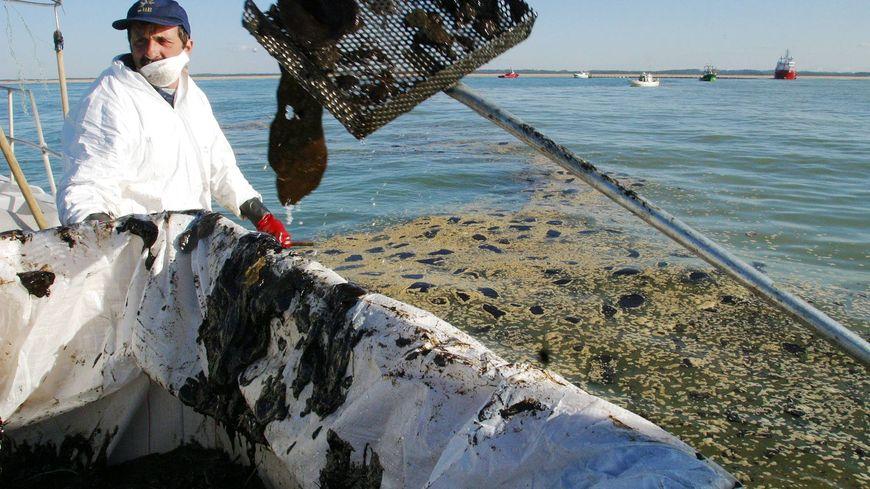 Un bateau de pêche récupère le pétrole du Prestige en mer, en 2003.