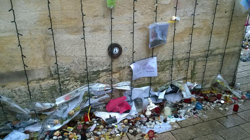Au pied de la porte Guillaume, les messages, bougies et fleurs prennent l'eau