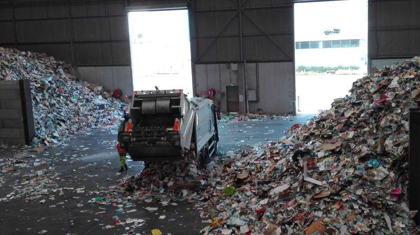 Les agents de collecte déchargent le contenu de leur camion, en vrac, dans le premier entrepôt de l'usine de tri - Radio France