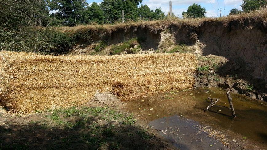 Deux kilomètres en aval de la station d'épuration de Gouzon, des bottes de paille de haute densité servent de barrage filtrant sur La Voueize