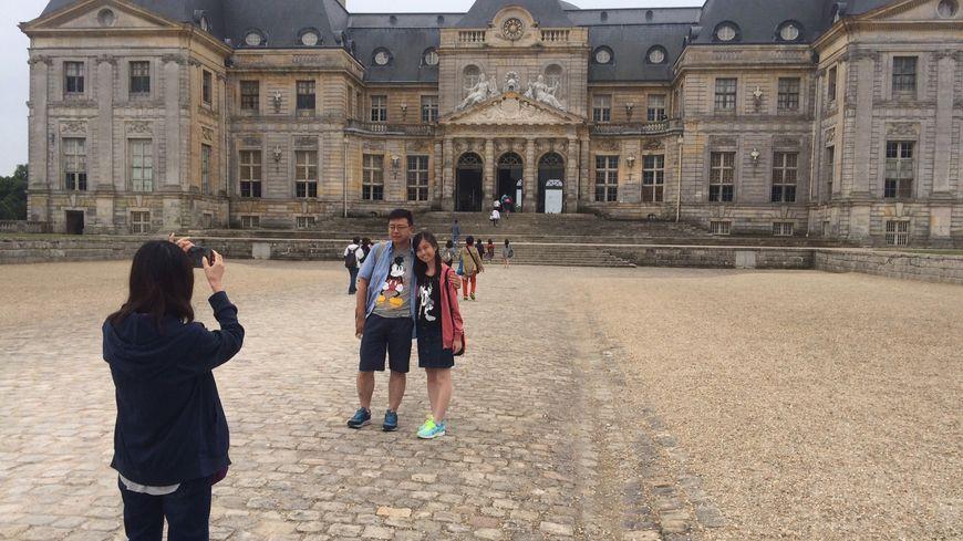 Des touristes japonais se prennent en photo devant le Château de Vaux-le-Vicomte