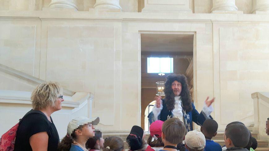 Le roi Louis XIV accueille les enfants venus visiter Versailles