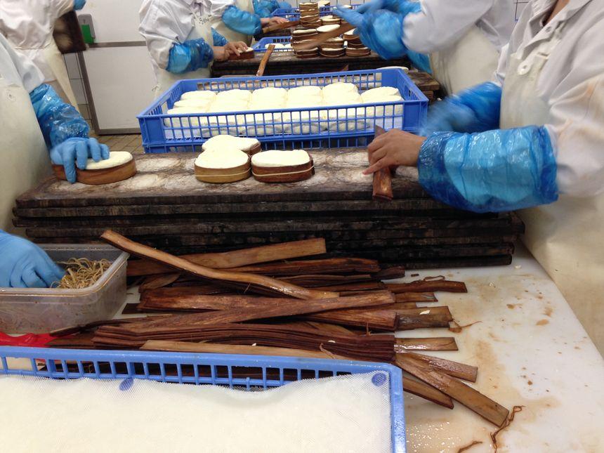 Une dizaine de personnes sanglent les fromages avec de l'épicéa  - Radio France