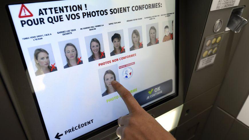 Une personne réalise, dans un Photomaton, une série de photographies d'identité conformes pour les documents officiels français.