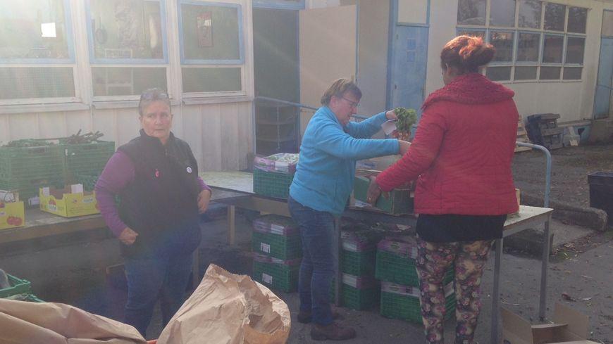 Les bénévoles s'activent devant le centre pour distribuer des légumes aux premiers inscrits.
