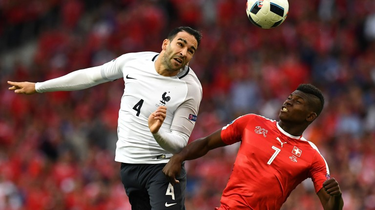 France's defender Adil Rami (L) vies for the ball against Switzerland's forward Breel Embolo during the Euro 2016 group A football match between Switzerland and France at the Pierre-Mauroy stadium in Lille on June 19, 2016. / AFP PHOTO / FRANCK FIFE