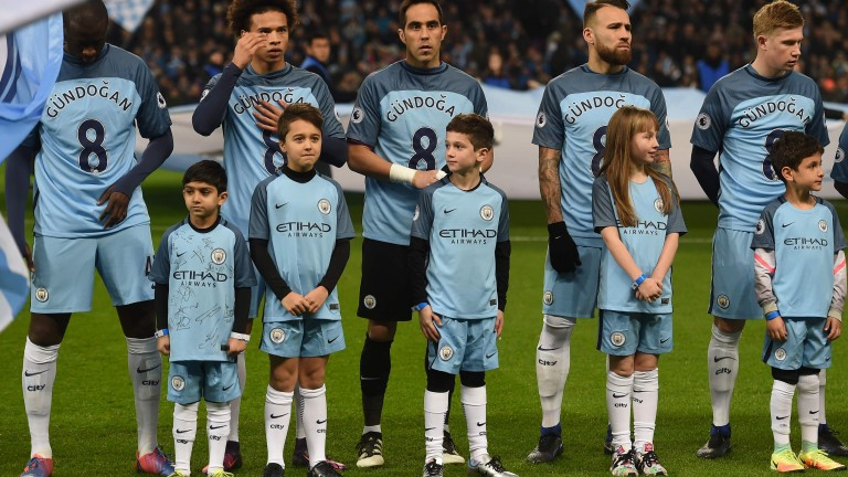 Manchester City's players wear special shirts with the number of Manchester City's German midfielder Ilkay Gundogan on the front ahead of the English Premier League football match between Manchester City and Arsenal at the Etihad Stadium in Manchester, north west England, on December 18, 2016.