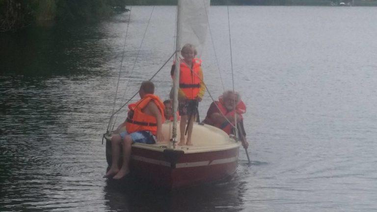 Die Familien haben Spaß bei dem kleinen Segeltörn auf dem See