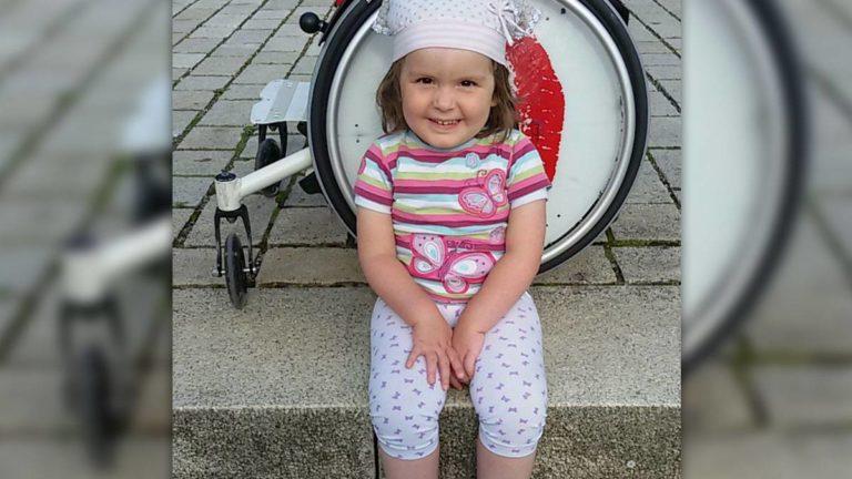 Die kleine Elisa vor ihrem Rollstuhl