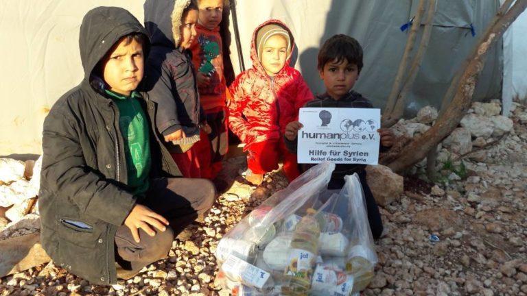 Kinder in einem Flüchtlingscamp im Umland von Aleppo mit den gelieferten Lebensmitteln.