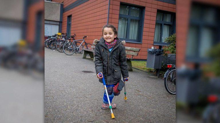 Moazama (9) auf ihren Krücken vor dem Krankenhaus in Düsseldorf