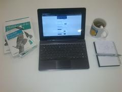 Android tablet docked into a keyboard on a desk surrounded by books, a notepad and a cup of green tea in a Mr Happy mug showing a mobile website with reduced functionality.