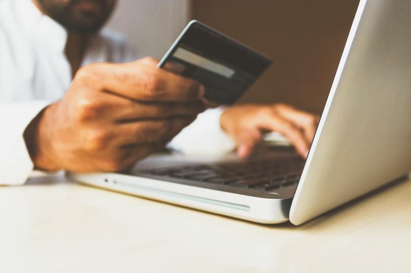 Uomo con carta di credito in mano che digita al computer