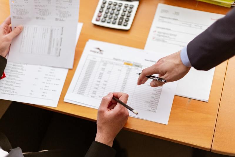 mani con penna tavolo con documenti di contabilità