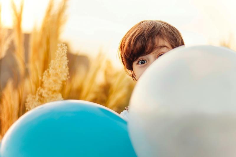 Bambino con palloncini colorati