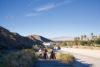 cult crew walking bikes up ditch desert hot springs