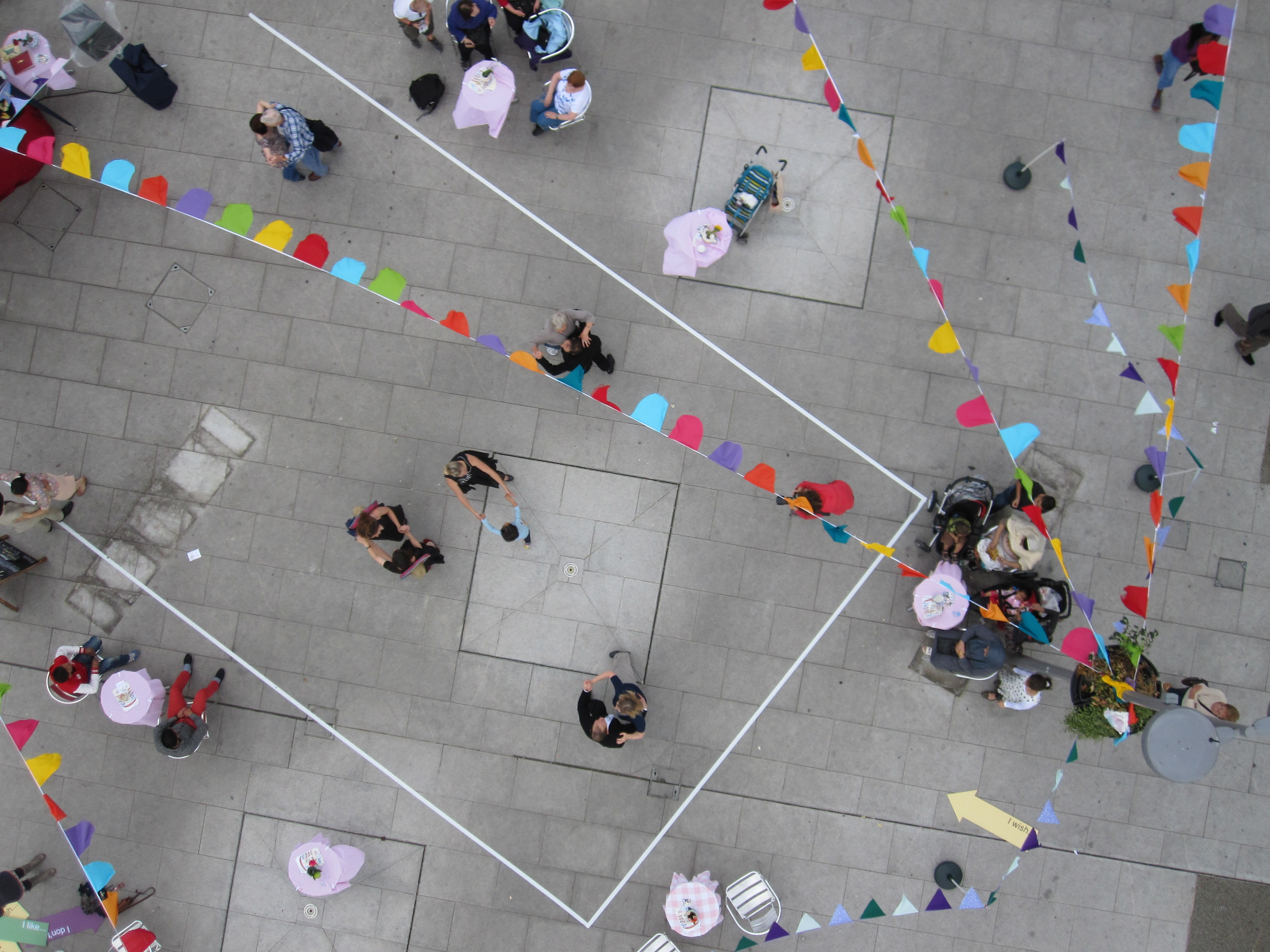 Arial view of people dancing and sitting outside underneath bunting in Wood Green, London.
