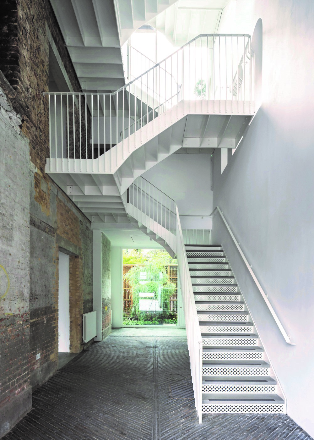 The inside of a converted fire station showing a modern stairwell against an old brick wall.