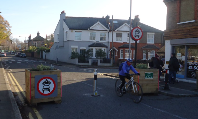 Image of King Charles Low Traffic Neighbourhood. Image of cyclist on the road in between two planter blocking the road to traffic but not cyclists and pedestrians