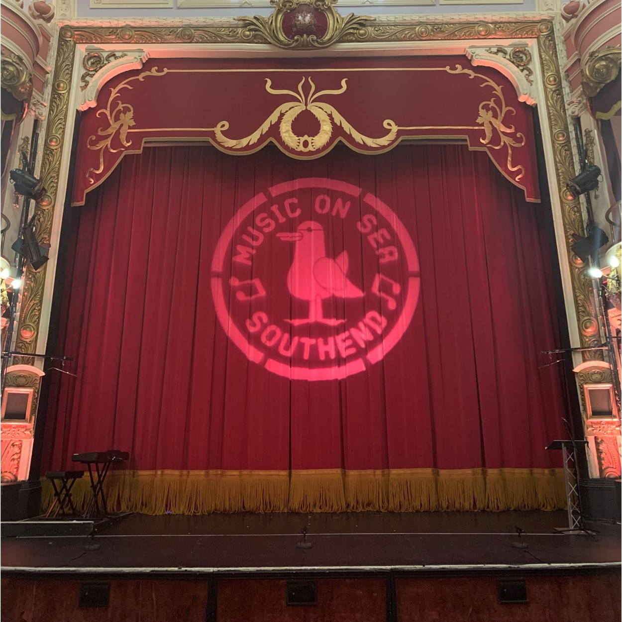 stage with closed curtain displaying the Music on Sea logo