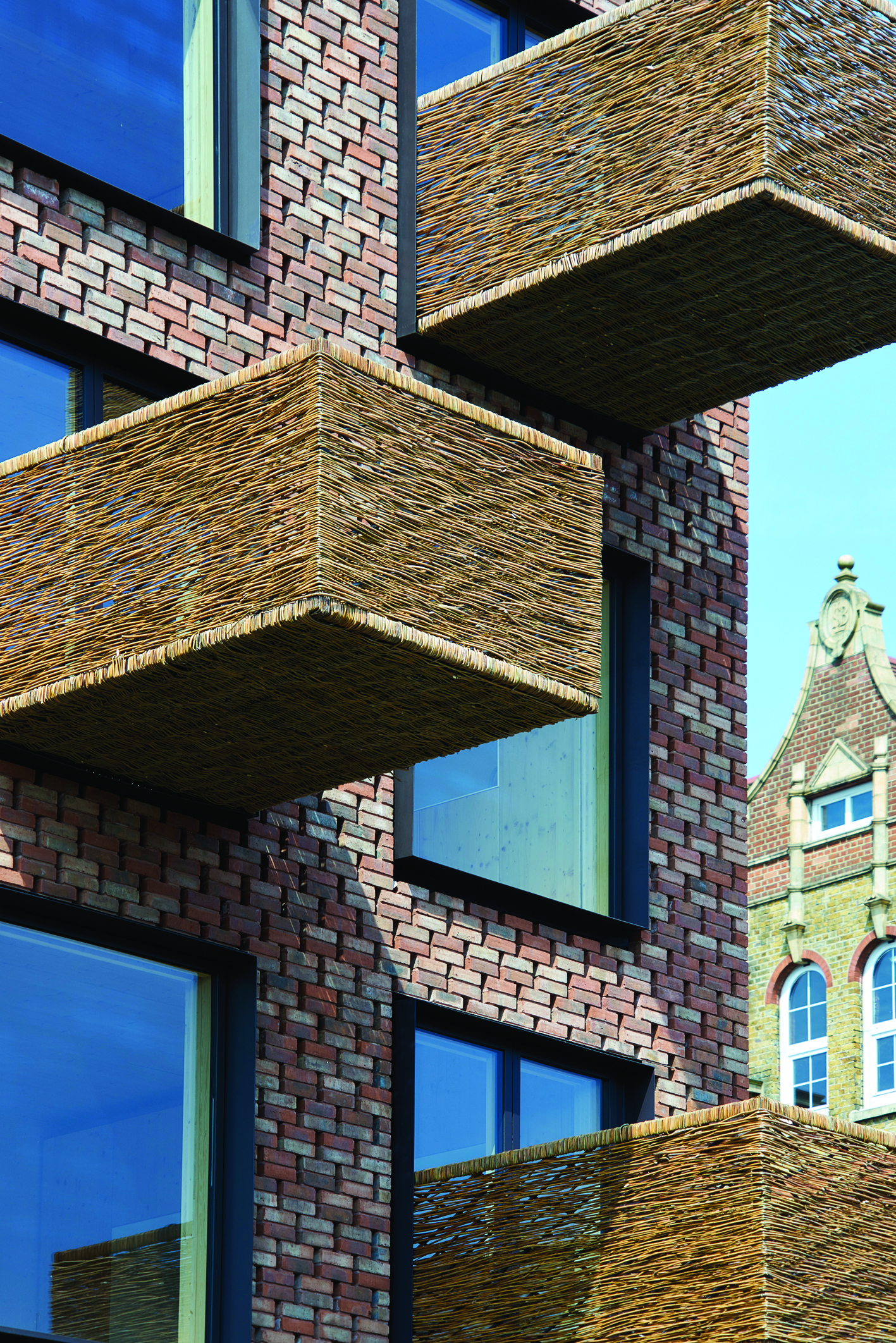 Wicker-covered balconies alternating in positions on the outside of Barretts Grove flatted development.