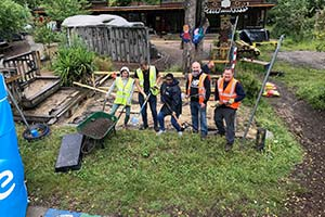 Volunteering team posing with garden tools