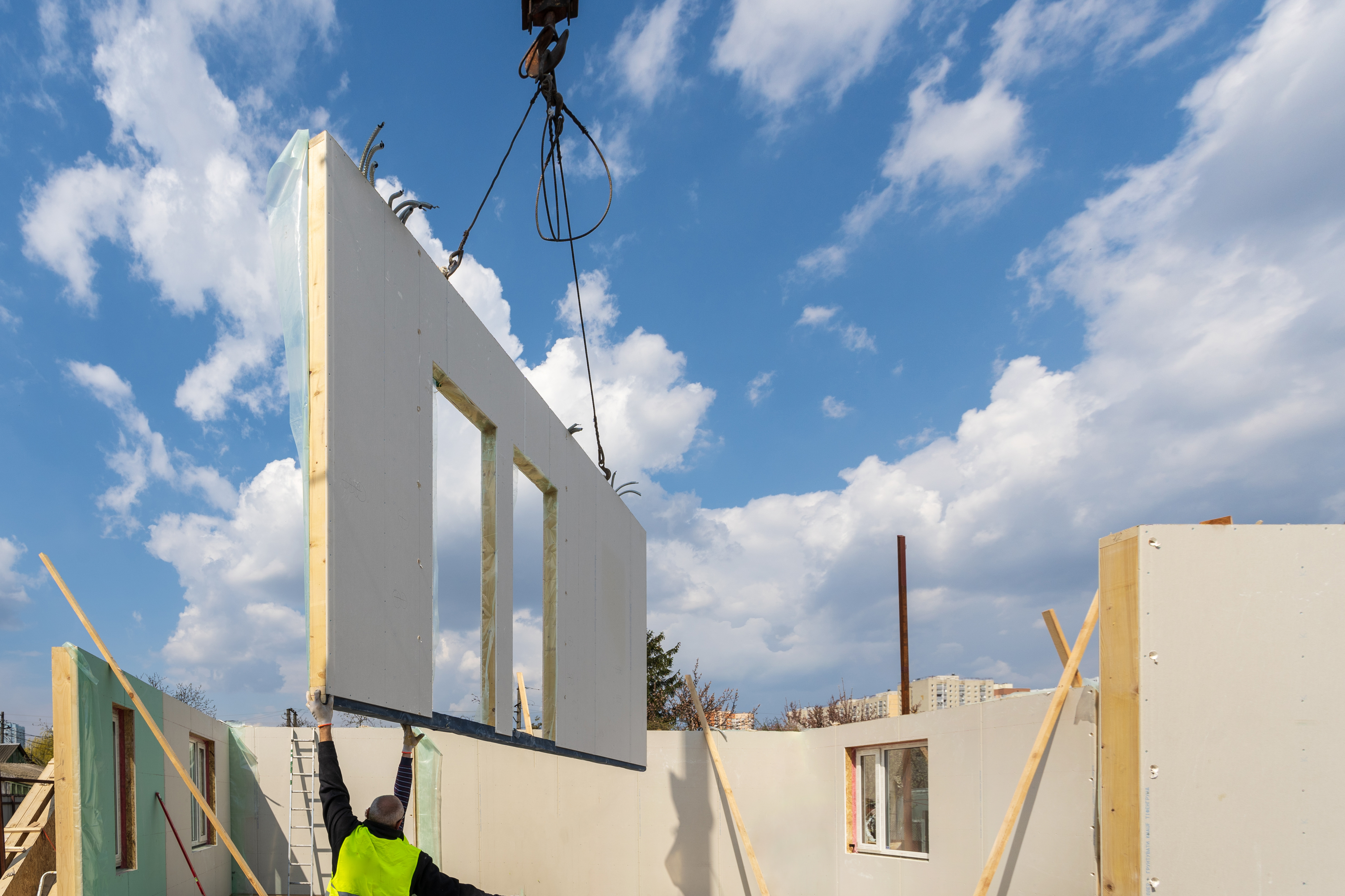 A construction site showing modular construction with a panel being lifted by a crane to fit one side of a building.