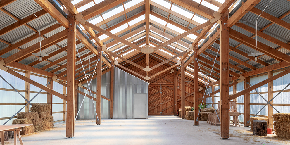 The inside of a building showing timber frames and light coming through the roof. It is set-up as an event space with hay bales and tables and chairs.