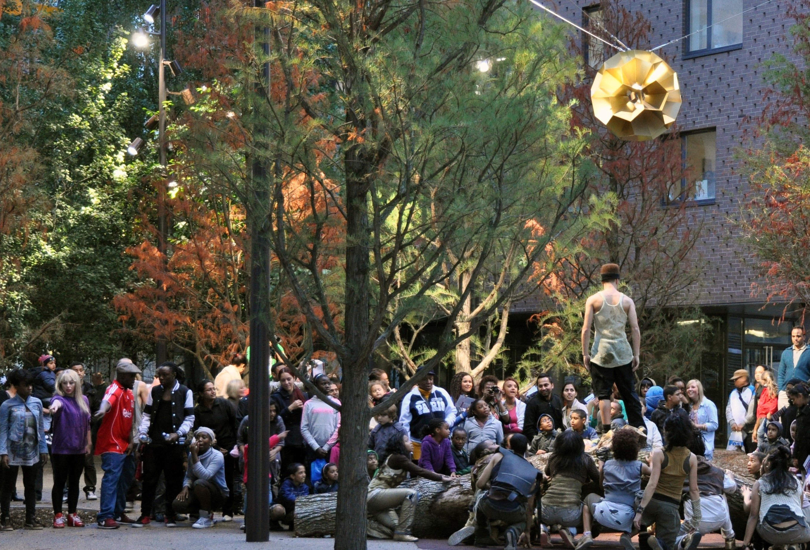A group of artists performing in a public open space surrounded by buildings. A large crowd is watching the performance.