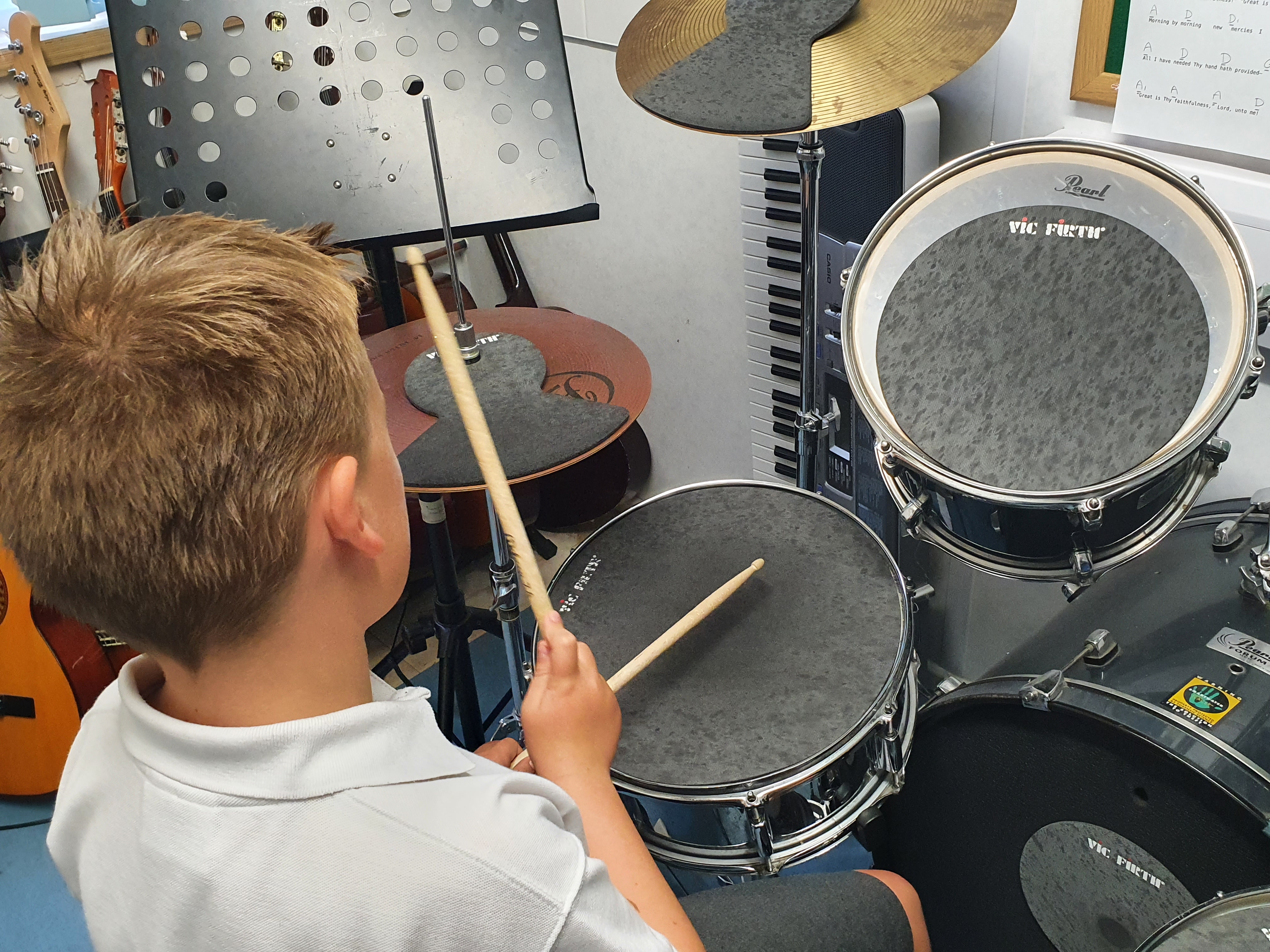 student playing a drum kit