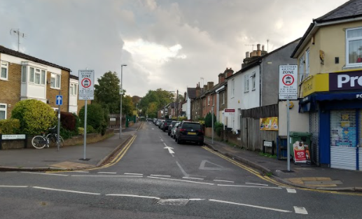 Image of Princes Road School Street taken from the junction at the top of the road, looking down towards trees at the bottom of the Street and with houses and parked cars visible on the right hand side of the Street.