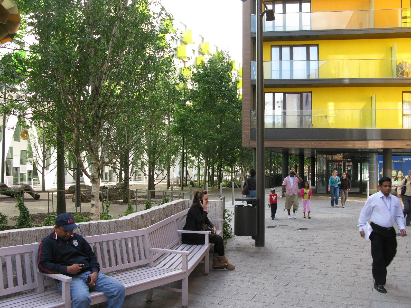 People sitting on a long bench and walking through Barking Town Centre, with residential development and trees in the background.