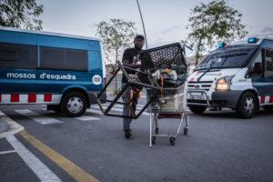Una persona d'origen subsaharià recull ferralla a Barcelona entre furgones dels Mossos d'Esquadra / JORDI BORRÀS