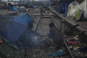 Dos homes descansen al costat de les vies del tren prop del camp de refugiats d'Idomeni, a la frontera de Grècia amb Macedònia. Foto: Xavi Herrero