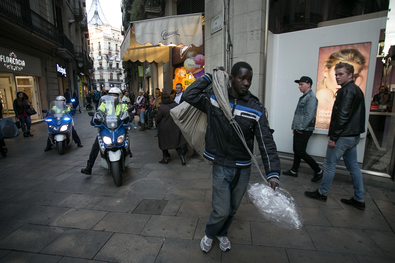 Venedor ambulant a Barcelona desmunta la parada davant la presència de la Guàrdia Urbana / CARLOS MORENO
