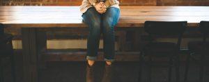 Female sat on a wooden desk, highlighting speaker anxiety