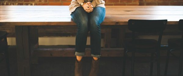 Female sat on a wooden desk, highlighting speaker anxiety