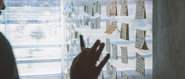 Man placing post-it notes on wall