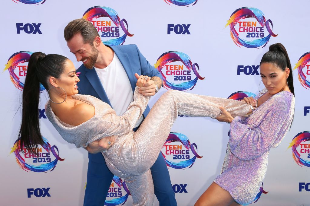 Retired US wrestlers Nikki Bella (L) and Brie Bella (R) and Russian-US dancer Artem Chigvintsev (C) attend the 2019 Teen Choice Awards. (Photo: JEAN-BAPTISTE LACROIX/AFP/Getty Images)