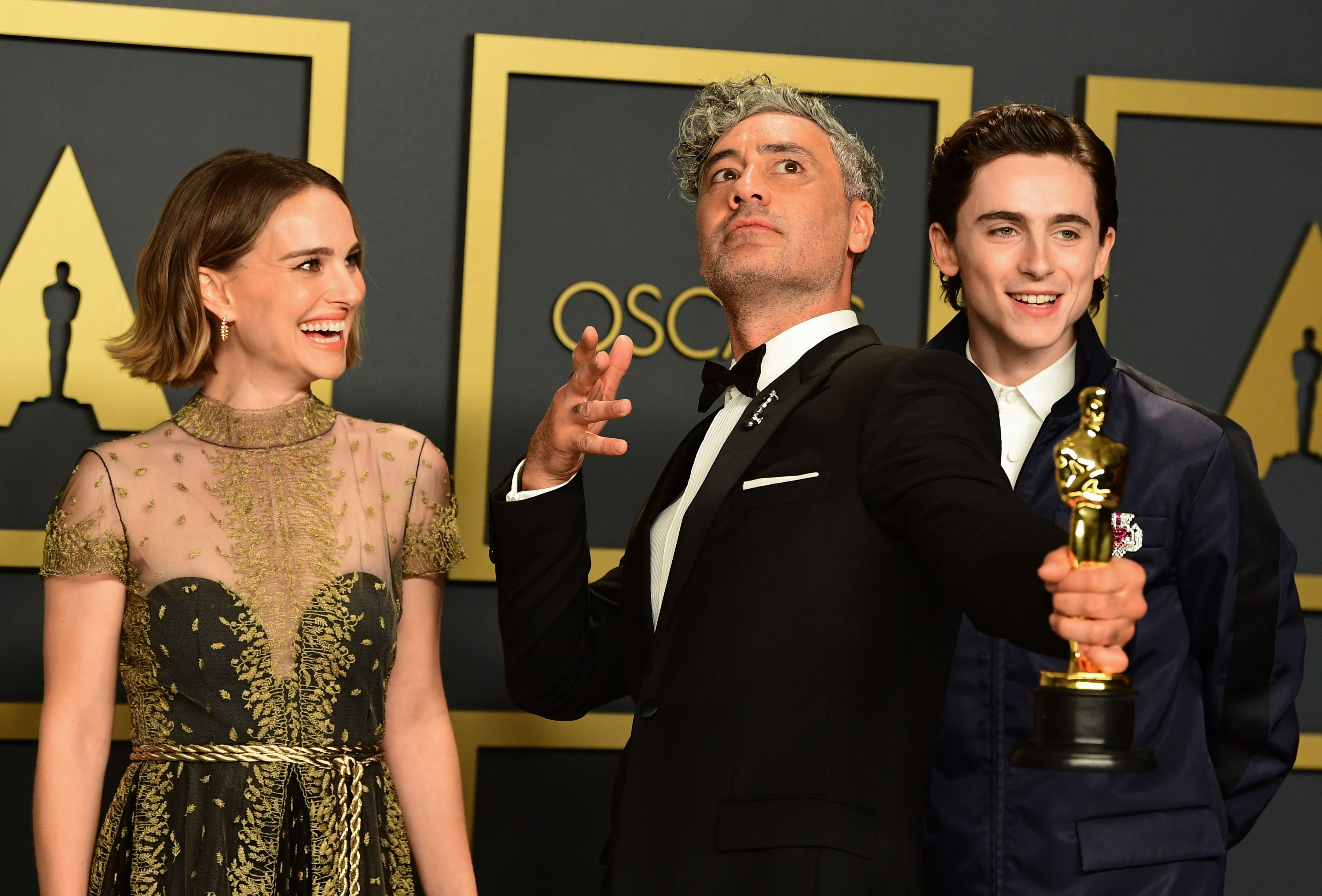 """Winner of Best Adapted Screenplay for """"Jojo Rabbit"""" New Zealand director Taika Waititi poses in the press room with US-Israeli actress Natalie Portman and US-French actor Timothee Chalamet during the 92nd Oscars at the Dolby Theater in Hollywood, California on February 9, 2020. (Photo by FREDERIC J. BROWN / AFP) (Photo by FREDERIC J. BROWN/AFP via Getty Images)"""