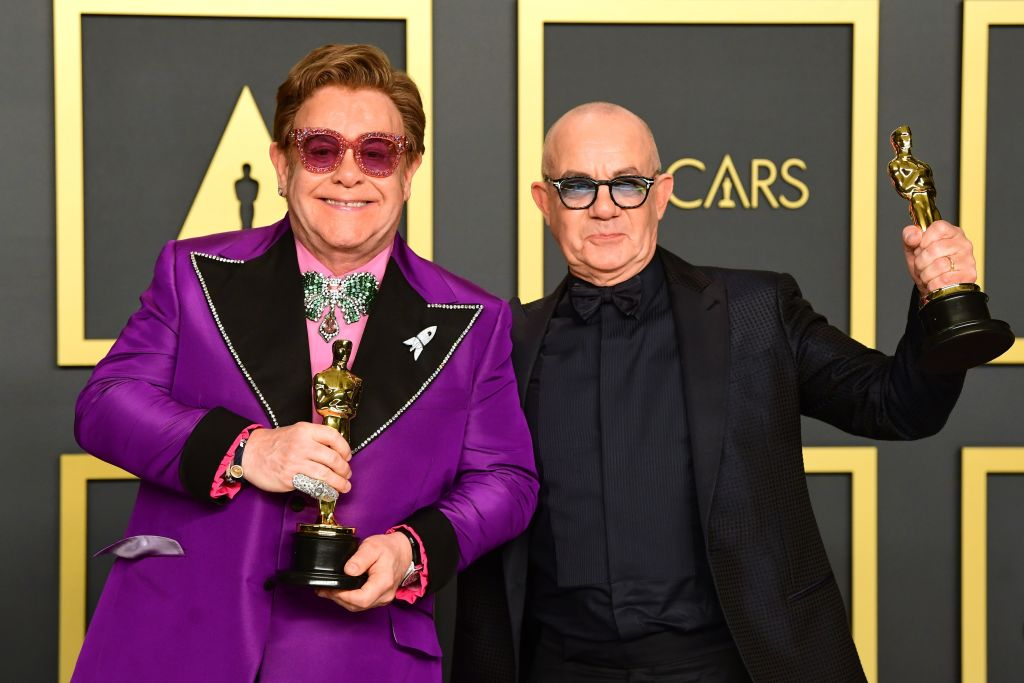 """British singer-songwriter Elton John (L) and British lyricist Bernie Taupin pose in the press room with the Oscar for Best Original Song for """"(I'm Gonna) Love Me Again, 'Rocketman'"""" during the 92nd Oscars at the Dolby Theater in Hollywood, California on February 9, 2020. (Photo by FREDERIC J. BROWN / AFP) (Photo by FREDERIC J. BROWN/AFP via Getty Images)"""