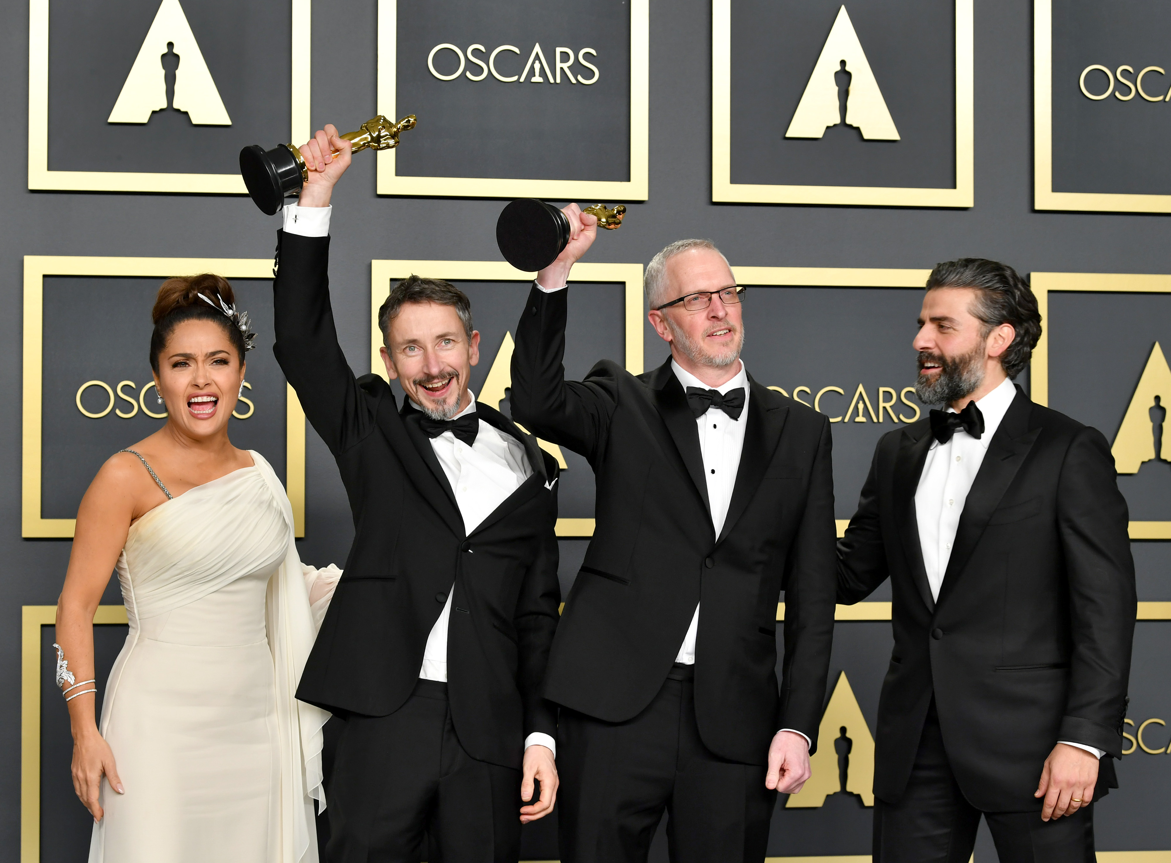 """Sound editors Mark Taylor and Stuart Wilson, winners of the Sound Mixing award for """"1917,""""  pose with Salma Hayek (L) and Oscar Isaac (R) in the press room during the 92nd Annual Academy Awards at Hollywood and Highland on February 09, 2020 in Hollywood, California. (Photo by Amy Sussman/Getty Images)"""