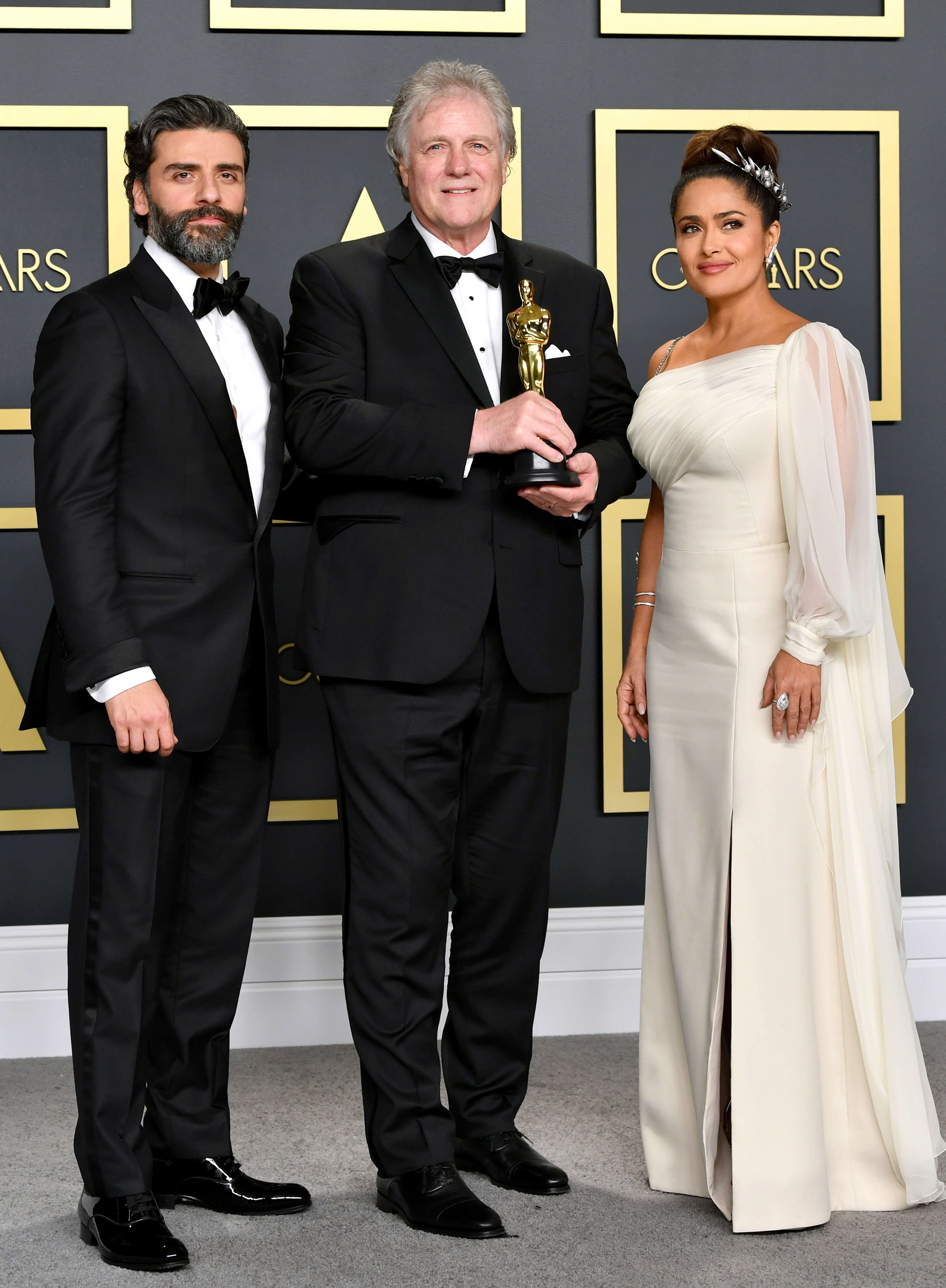 """Sound engineer Donald Sylvester, winner of the Sound Editing award for """"Ford v Ferrar,"""" poses with Oscar Isaac (L) and Salma Hayek (R) in the press room during the 92nd Annual Academy Awards at Hollywood and Highland on February 09, 2020 in Hollywood, California. (Photo by Amy Sussman/Getty Images)"""