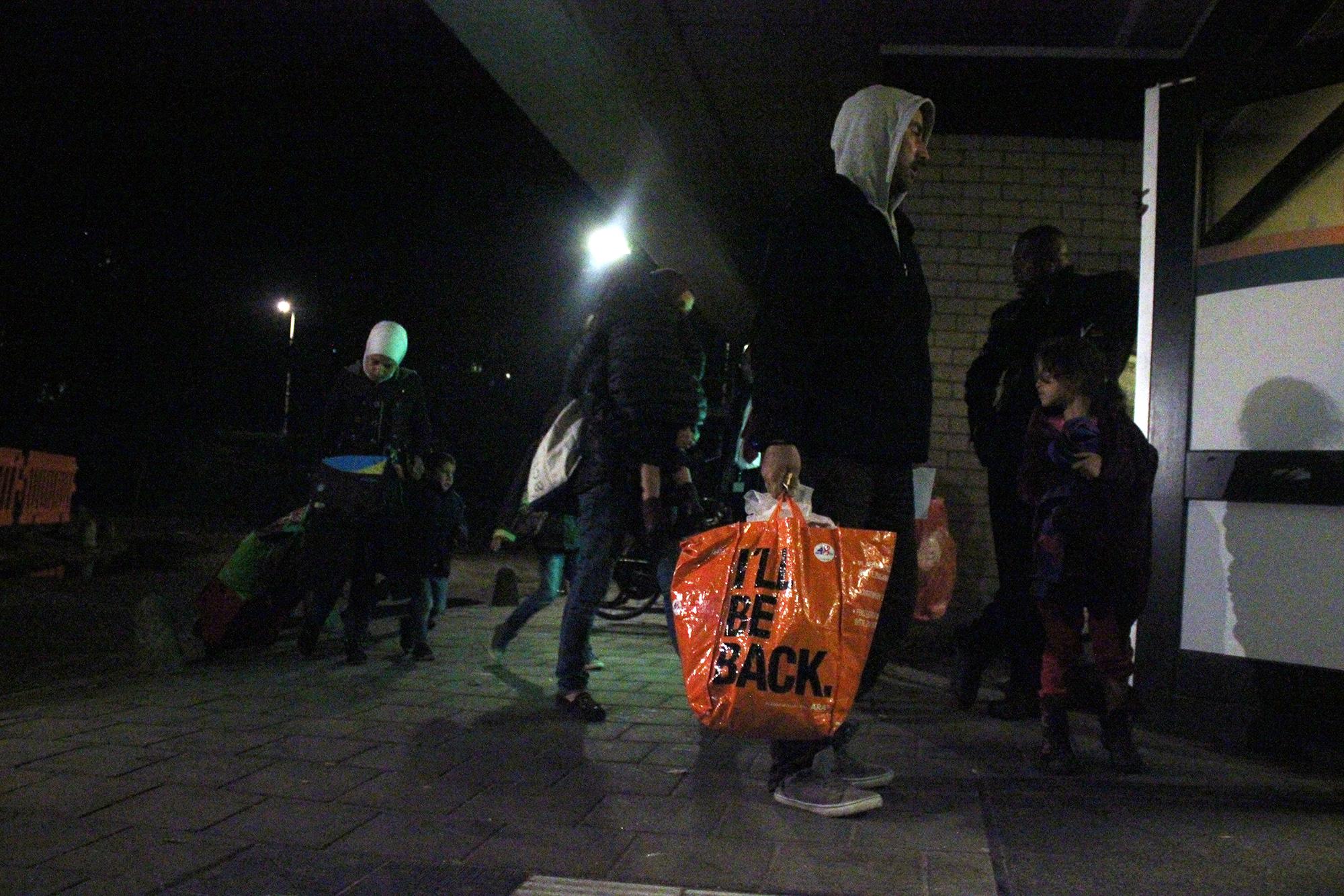 vluchtelingen komen aan in sportgebouw