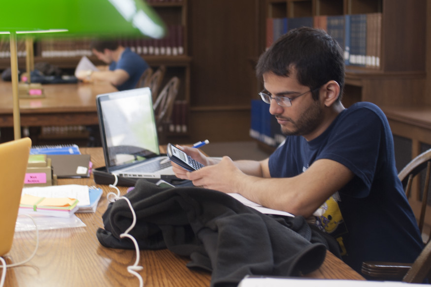 student achter laptop in bibliotheek