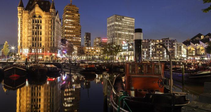Netherlands, South Holland, Rotterdam. Old Harbor skyline illuminated at dawn