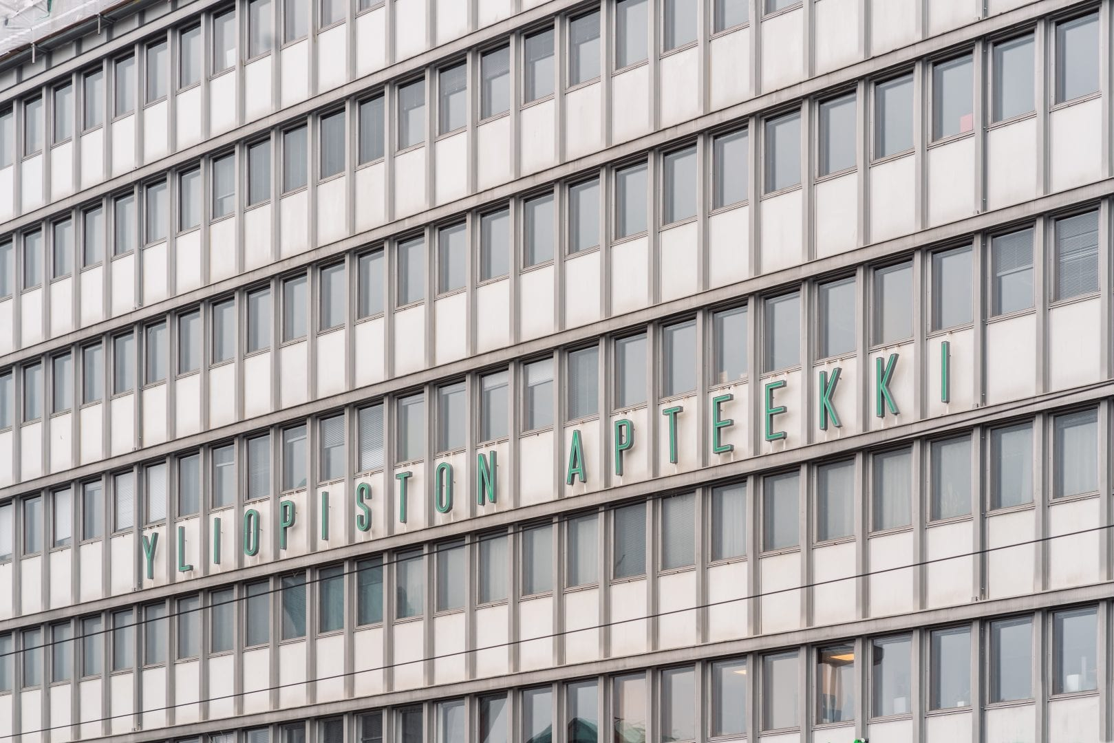 A closeup image of the Kaivotalo building in central Helsinki. It depicts 6 even rows of rectangular windows in a 60-degree perspective angle, most of which have blinders blocking the view. In the center, dark green letters spell the name of a pharmacy.